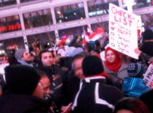 This woman's sign has a checklist: Tunisia and Egypt, two countries going through similar situations, are checked off.