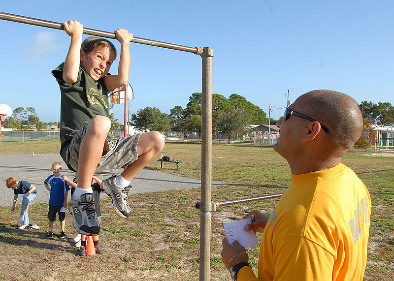 A child exercising on a chin-up bar.