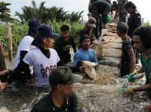 Thai military and volunteers work to repair a leak in a dike on the canal in On Nut, Bangkok. Image: Voice of America.
