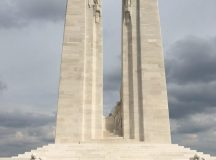 Photo of the enormous, striking and very moving Vimy War Memorial in France. There is a teenager in the foreground and the two towering spires of the monument in the background, against a light bluish-grey sky.