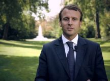 Emmanuel Macron. He is standing outside, with a fountain in the background. He is wearing a natty blue suit and tie. For some reason, he is also wearing a mic. I have no idea why, but it doesn't really affect the image which, essentially, is a nice photo ofMacron. Image: gouvernement.fr