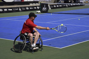 A tennis player in a red shirt and in a wheelchair is playing tennis on a blue tennis court. His right arm and racquet are outstretched and the ball is just about to hit his racquet.