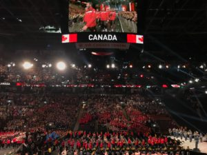 Team Canada enters the arena at the opening ceremony for the 2017 Invictus Games. The photo, which was shot from the stands above, shows a huge crowd of competitors on the lower floor level of the Air Canada Centre. Above them is jumbotron that says CANADA and shows some individual Canadian competitors. Photo: Joyce Grant, TKN