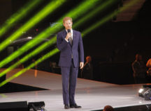 Prince Harry speaks at the opening ceremony of the 2017 Invictus Games in Toronto, Ontario. The photo shows him in a suit holding a microphone, talking. Behind him are green streaks of light (they are part of the decoration but they're pretty cool looking)