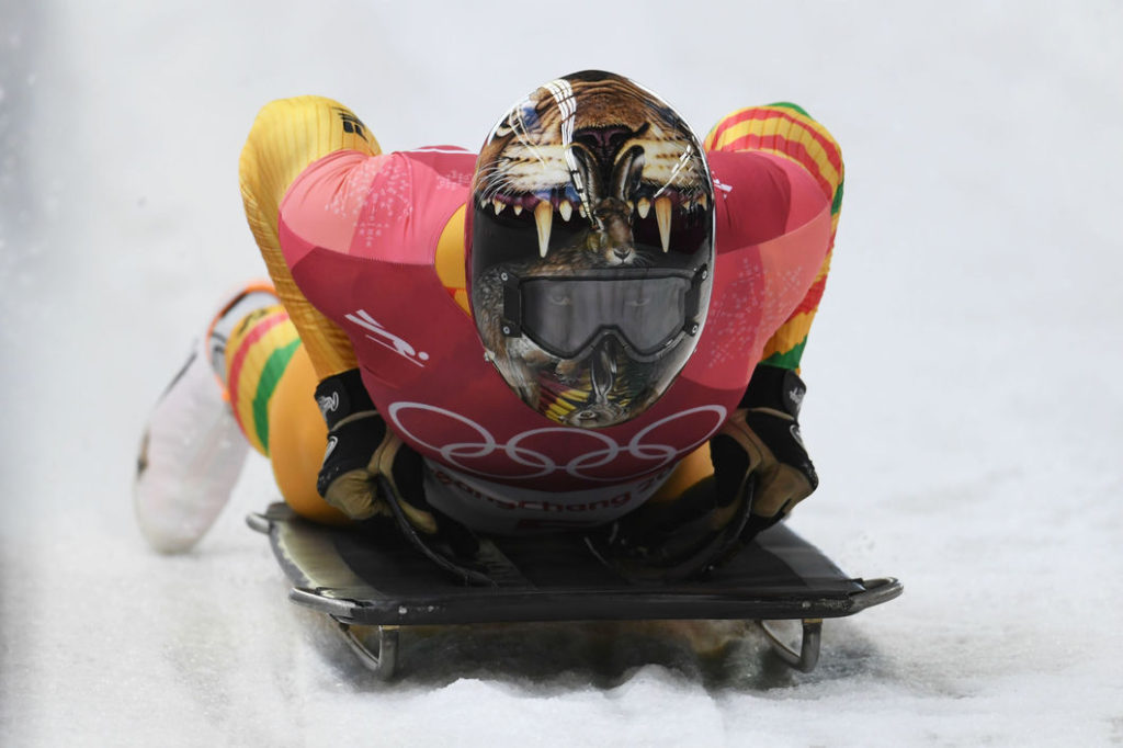 Photo of Akwasi Frimpong on a skeleton sled with a helmet that features a rabbit escaping from the jaws of a lion, symbolising his victory over adversity.