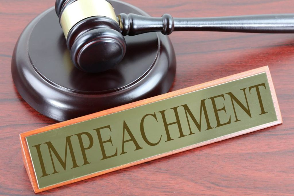 "A gavel and a sign that says ""impeachment"""