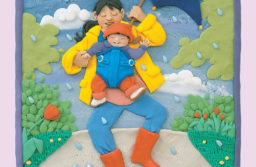 """Plasticine image of a mom and her baby under a beautiful blue umbrella, walking through a puddle in a rain shower. They are both smiling and happy. From """"Read me a Book"""" by Barbara Reid, published by Scholastic Canada Ltd., photograph by Ian Crysler."""