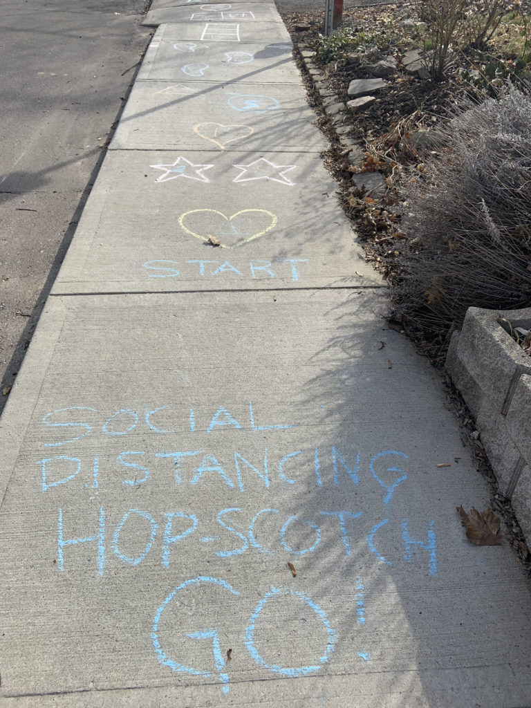 social distancing hopscotch; the image features a sidewalk with drawings that create a hopscotch activity