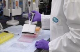 Image shows a Pfizer scientist working in a lab.